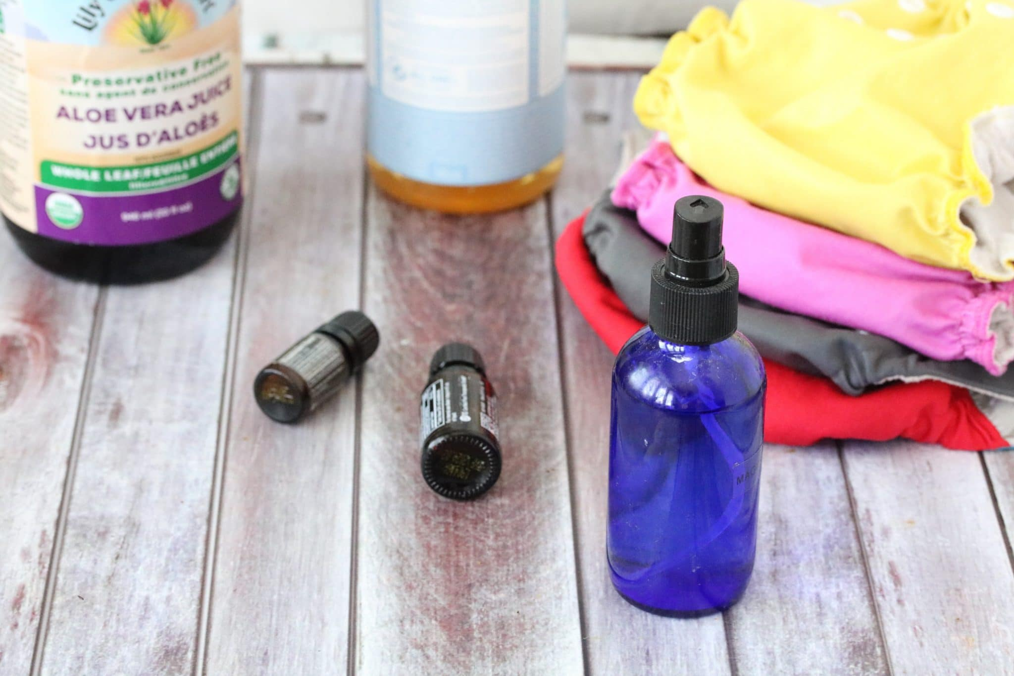 a cobalt blue bottle surrounded by ingredients like essential oils and aloe as well as cloth diapers