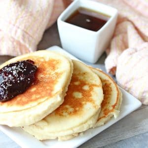 Three yogurt pancakes on a white plate topped with jam. Syrup in a white container behind it and a light orange napkin