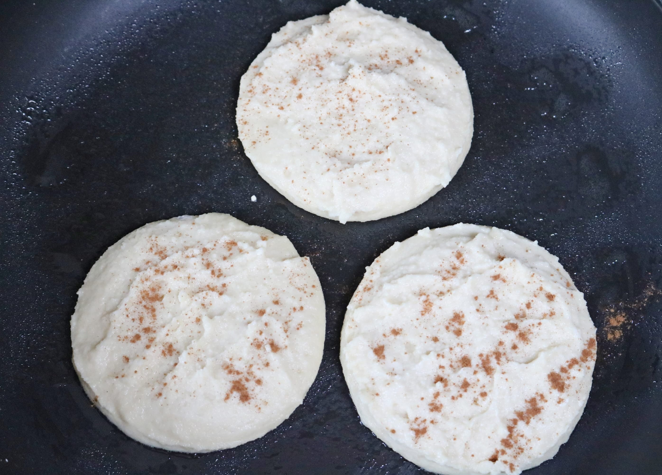 In process image for yogurt pancakes: three yogurt pancakes portioned into a pan to cook