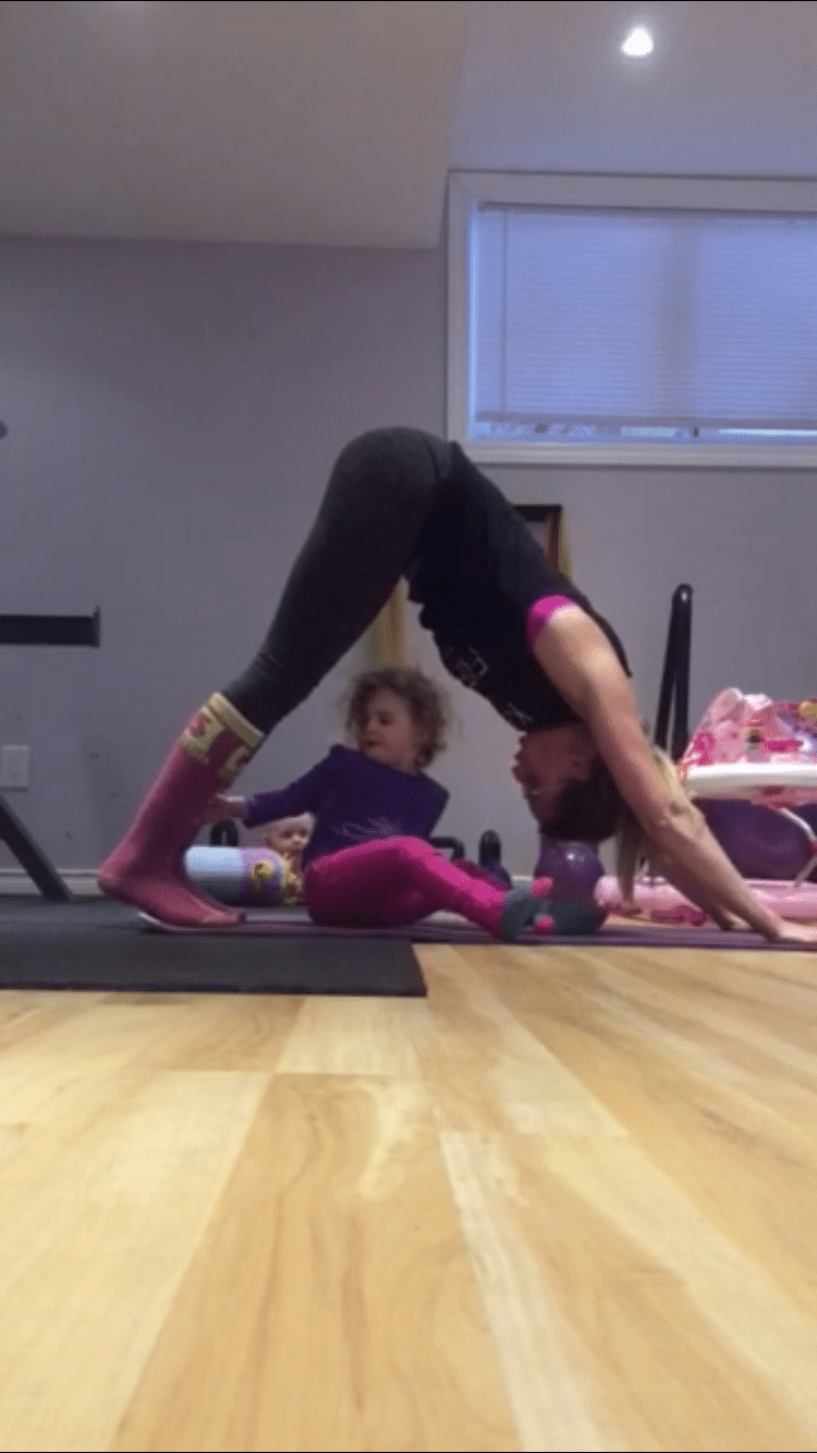 Mom in a down dog position in the gym with her toddler on the floor below her
