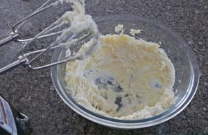 Diy whipped peppermint foot lotion, hardend ingredients in a bowl being whipped with mixer