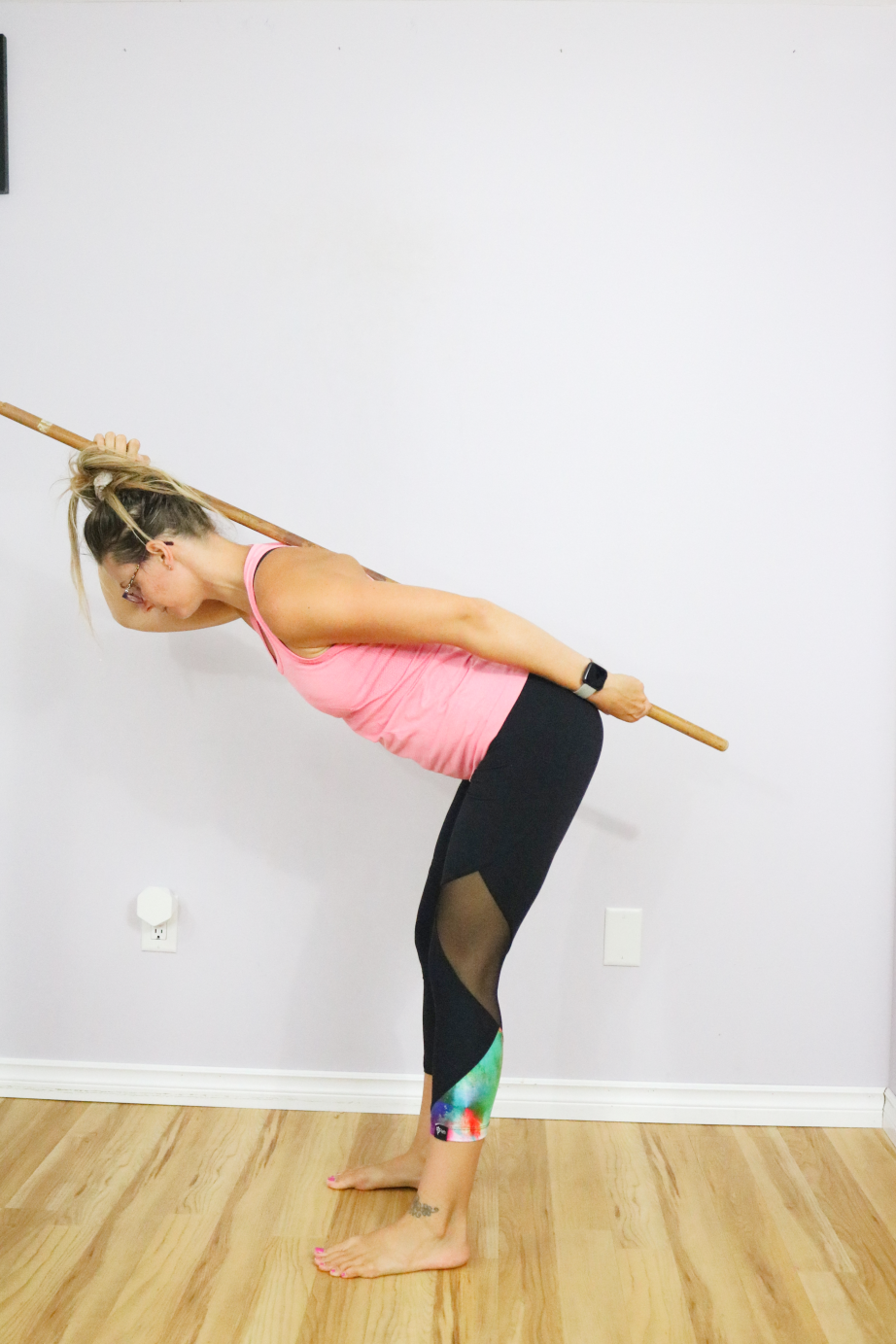 Woman in pink tank top and black pants learn how to perform a hip hinge with a dowel on her back