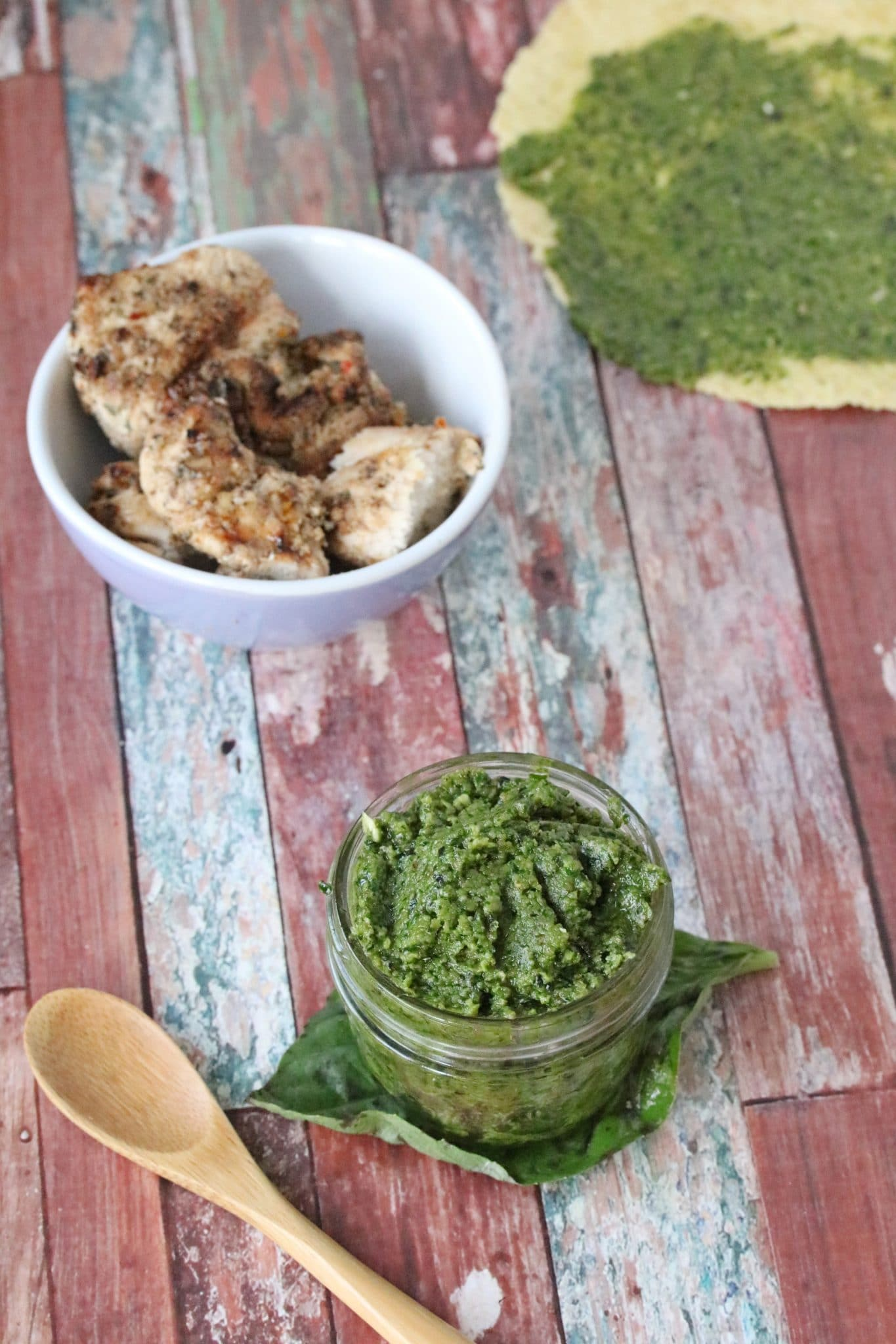 homemade basil pesto sauce in a mason jar with a wooden spoon and chicken around it