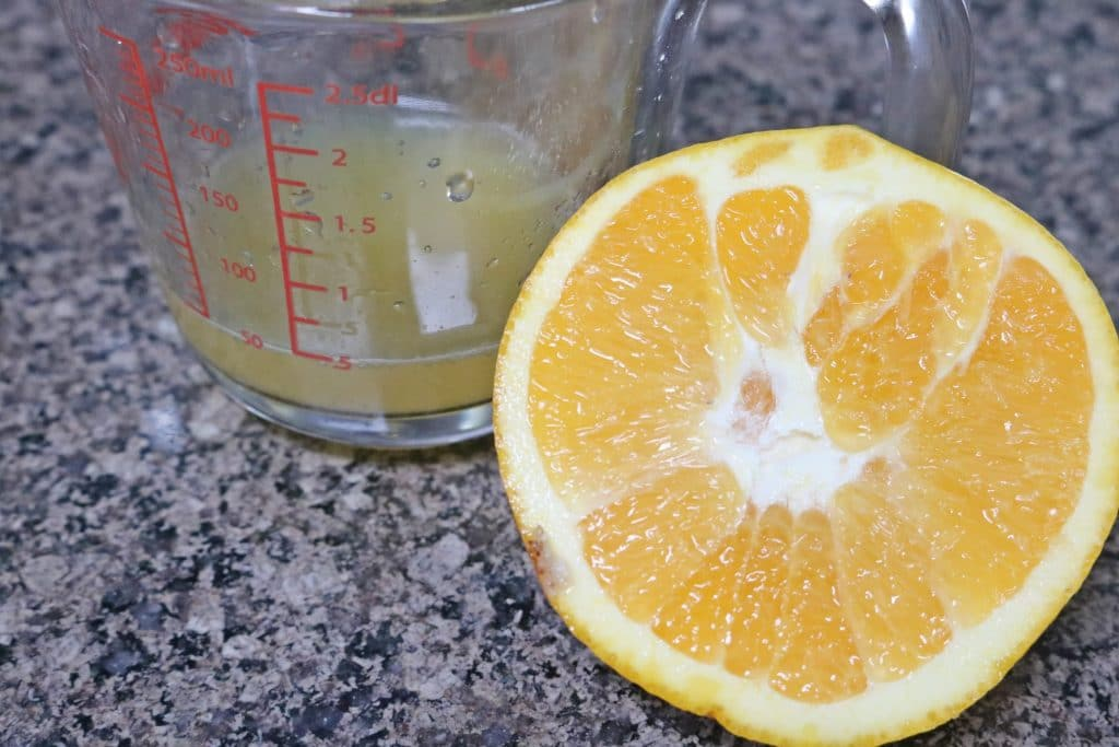 Half an orange next to a glass measuring cup with fresh orange juice
