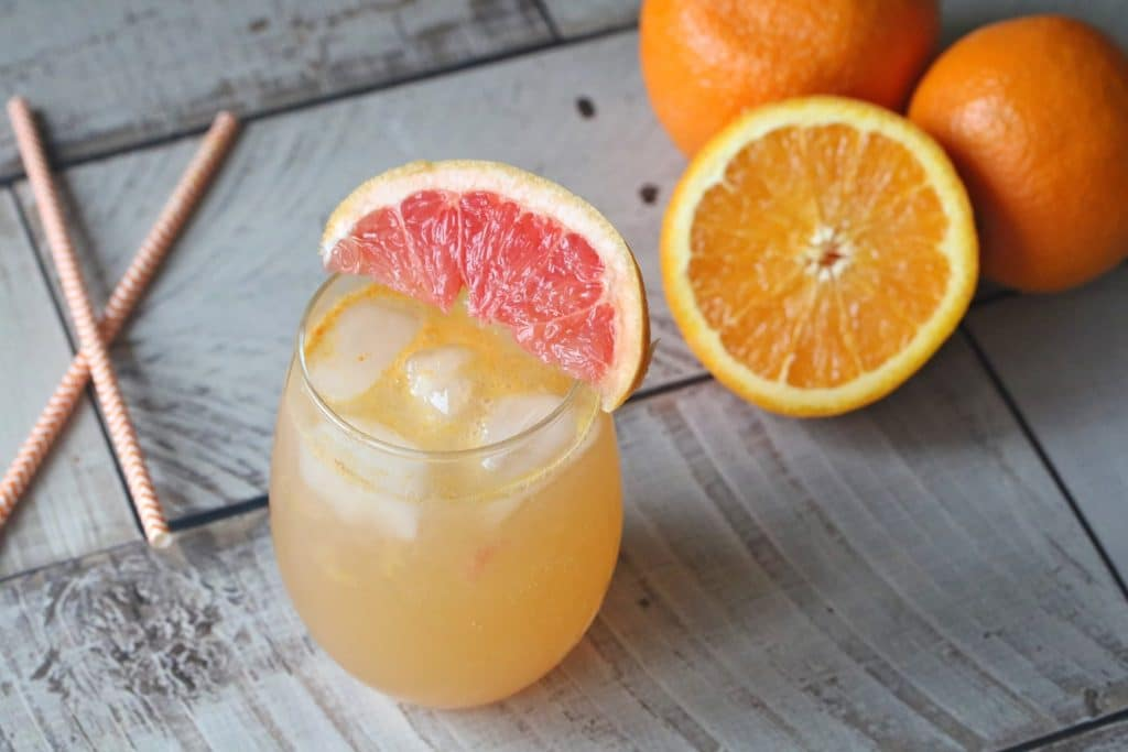 A healthy orange mocktail recipe in a glass garnished with grapefruit and straws beside it