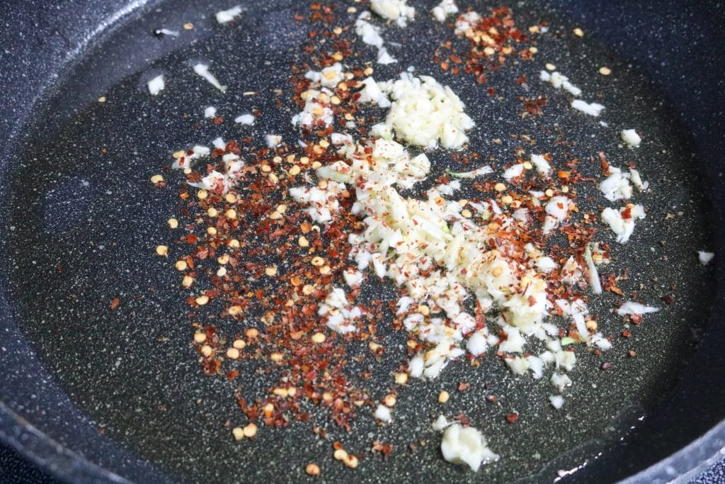 Garlic and chili flakes sauteing in oil in a large pan