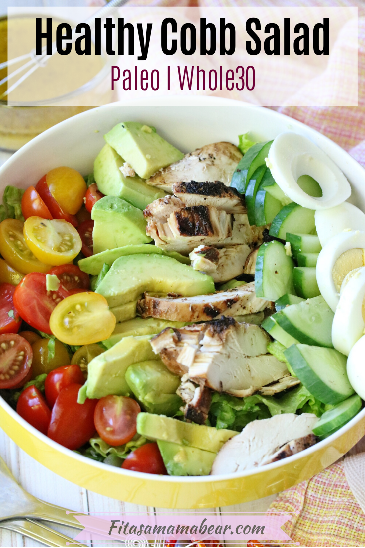 Pinterest image with text: whole30 cobb salad in a large yellow mixing bowl with a peach napkin and a measuring cup of dressing behind it