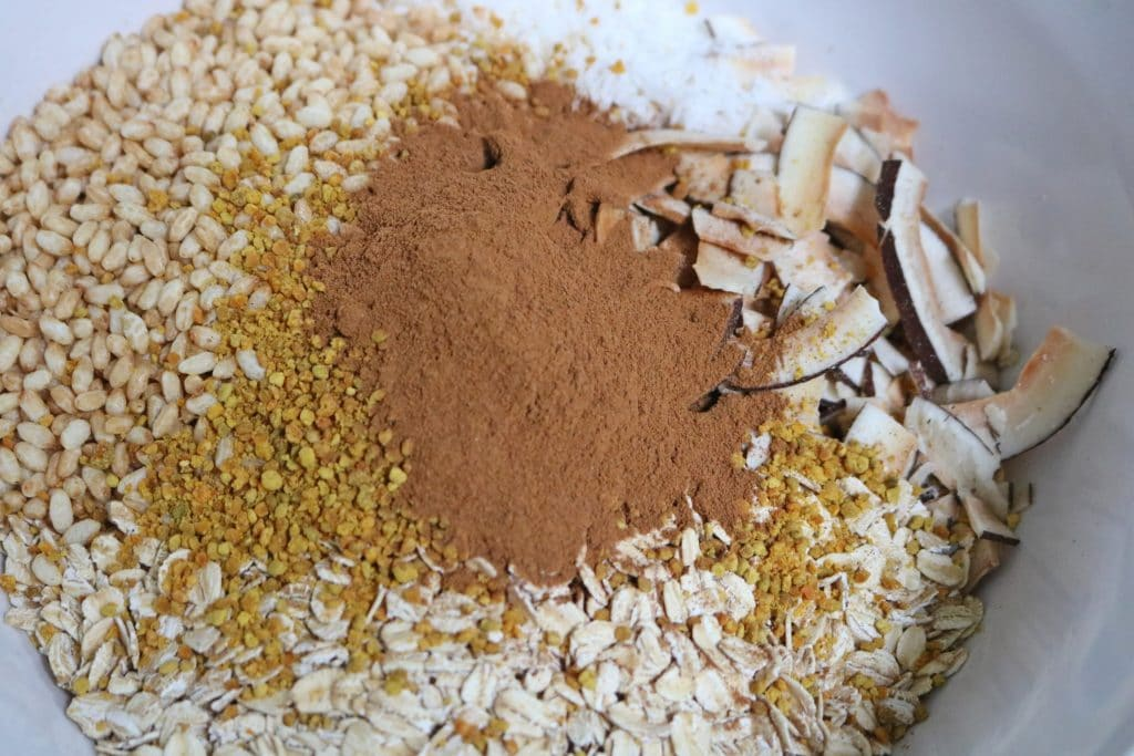 Rice puffs, cinnamon, coconut and bee pollen all combined in a large mixing bowl
