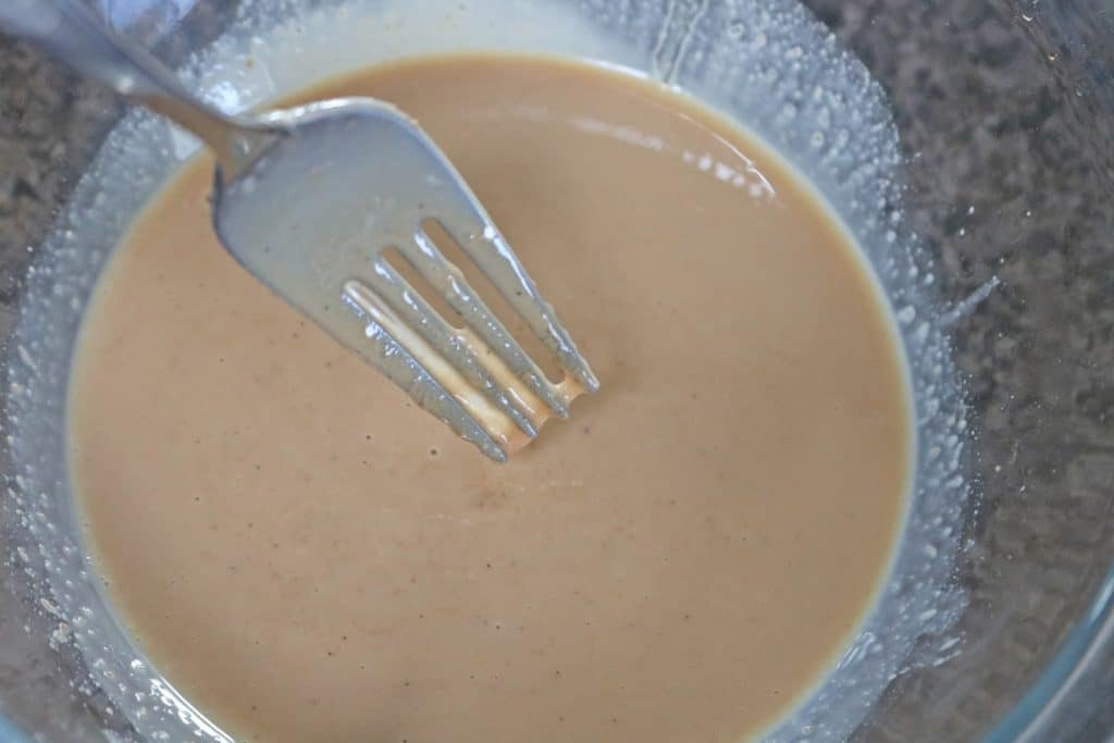 Nut butter and coconut oil melted together ina glass bowl with a fork
