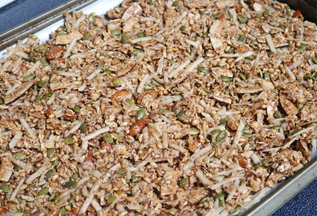 Apple pie granola spread out on a baking tray lined with parchment paper