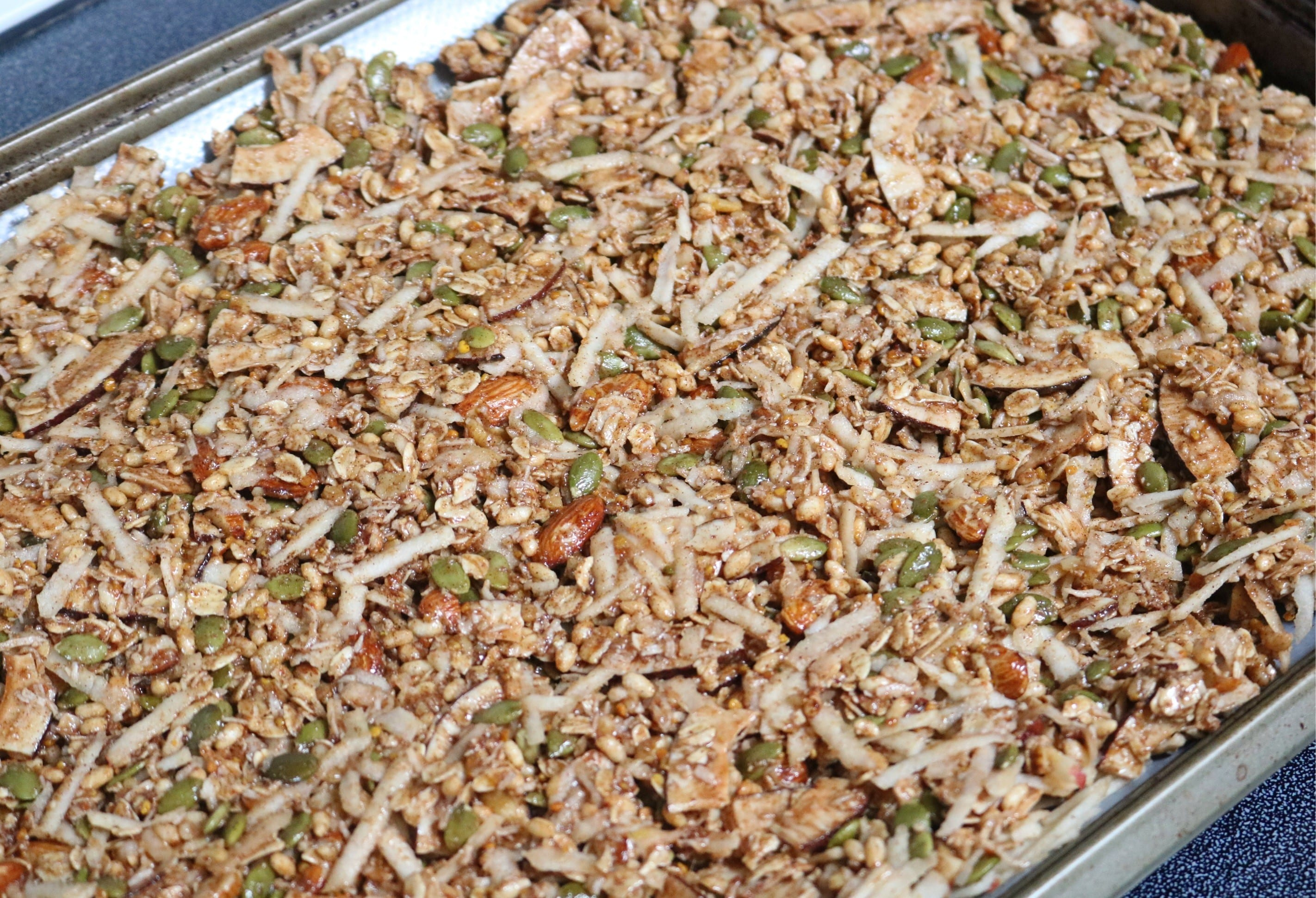 Apple pie granola on a baking tray lined with parchment paper