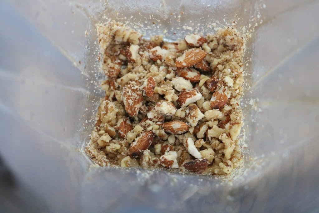 Walnuts and almonds in a blender being pulsed into chunks