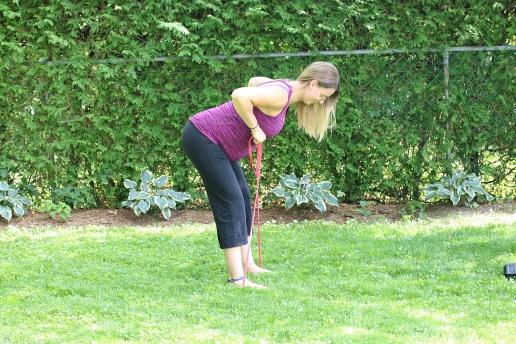 Pregnant woman in a purple shirt and black pants performing a resistance band exercise