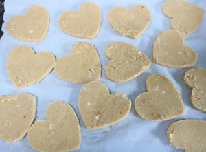 Coconut flour sugar cookies in heart shapes on parchment paper