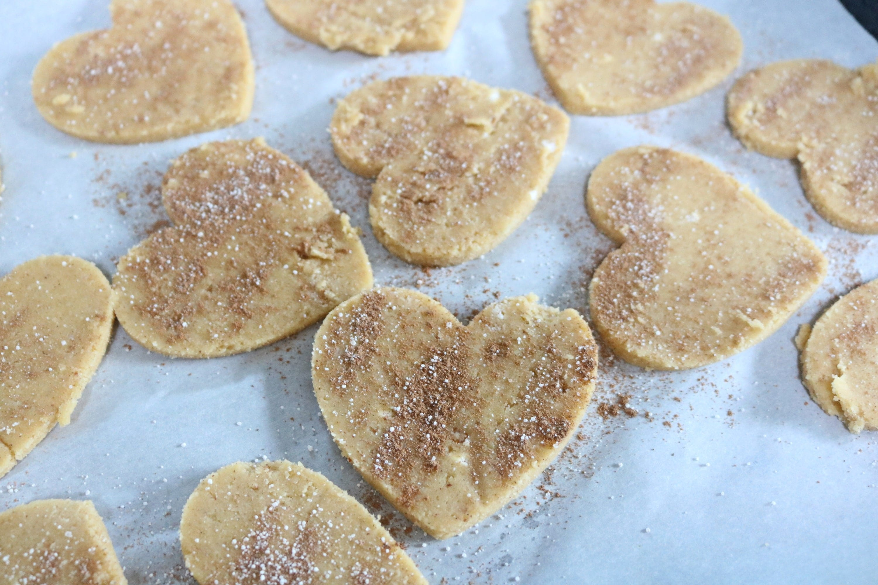 Heart shaped, gluten-free sugar cookies on parchment paper sprinkled with sugar and cinnamon