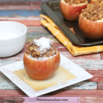 Featured image with text: stuffed apple with oatmeal filling on a white plate topped with coconut whip cream. White bowl beside it and more stuffed apples on a pan behind the plate
