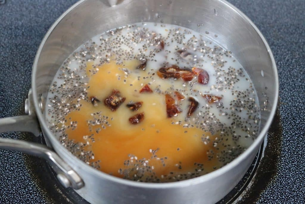 Oats, chia seeds, dates, and almond milk in a pot on the stove