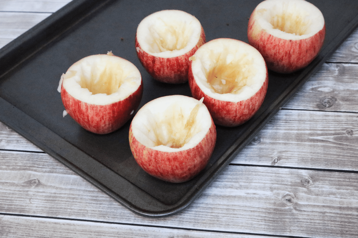 Apples that have been cored on a baking tray