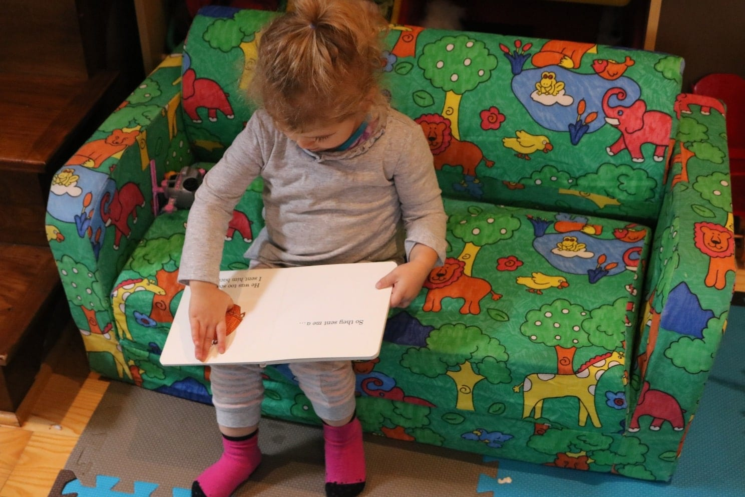 Toddler sitting on a toddler couch in a grey outfit reading a lift the flap book