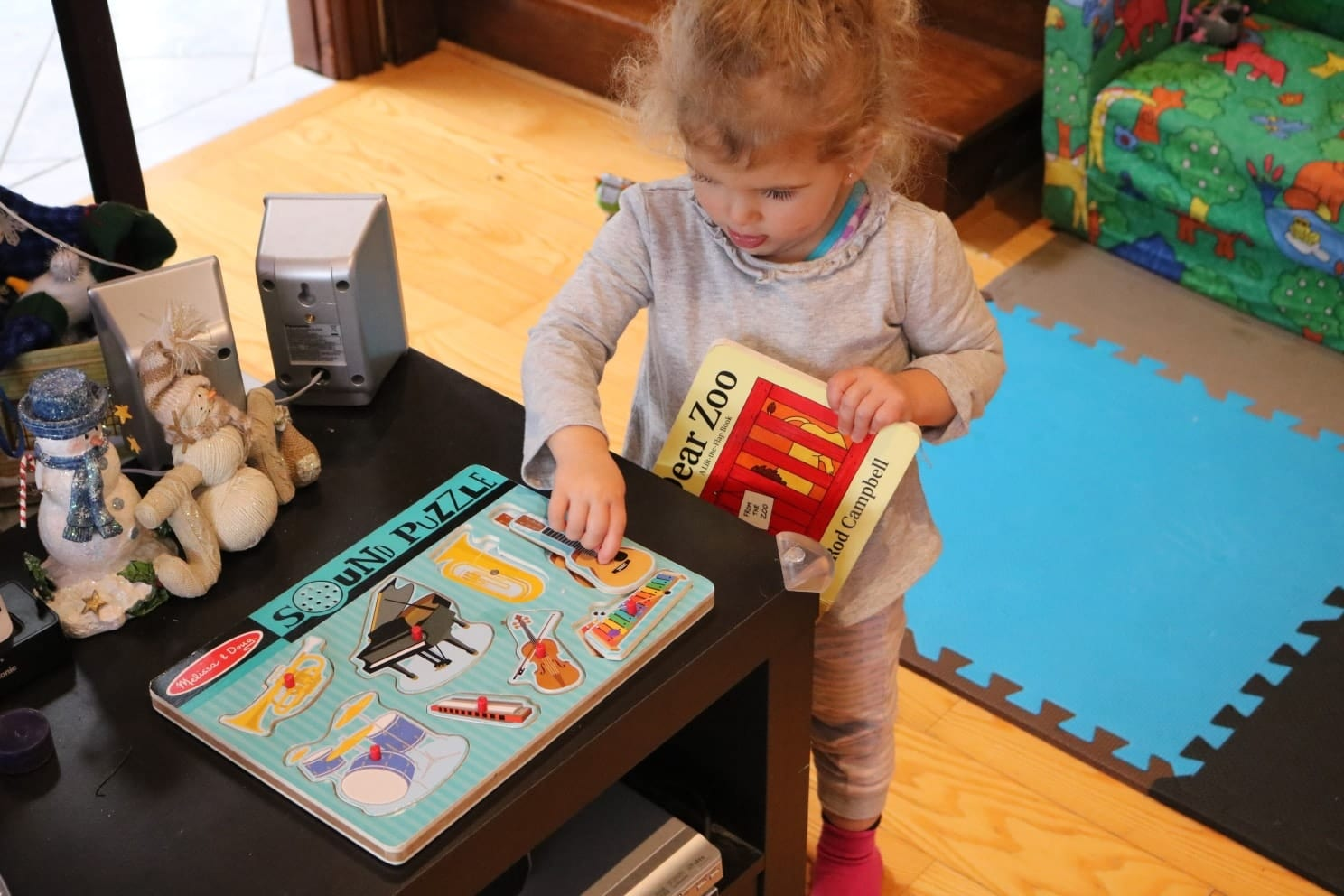 Toddler in a grey shirt playing with a noise puzzle while holding a book