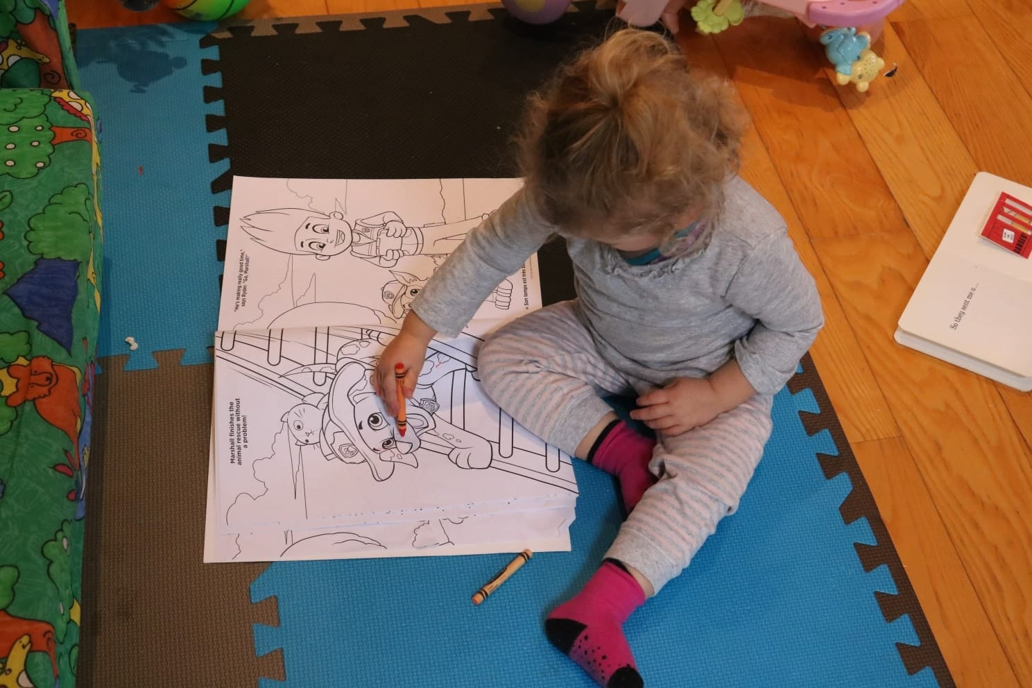 Toddler sitting on the floor with crayons and a paw patrol coloring book