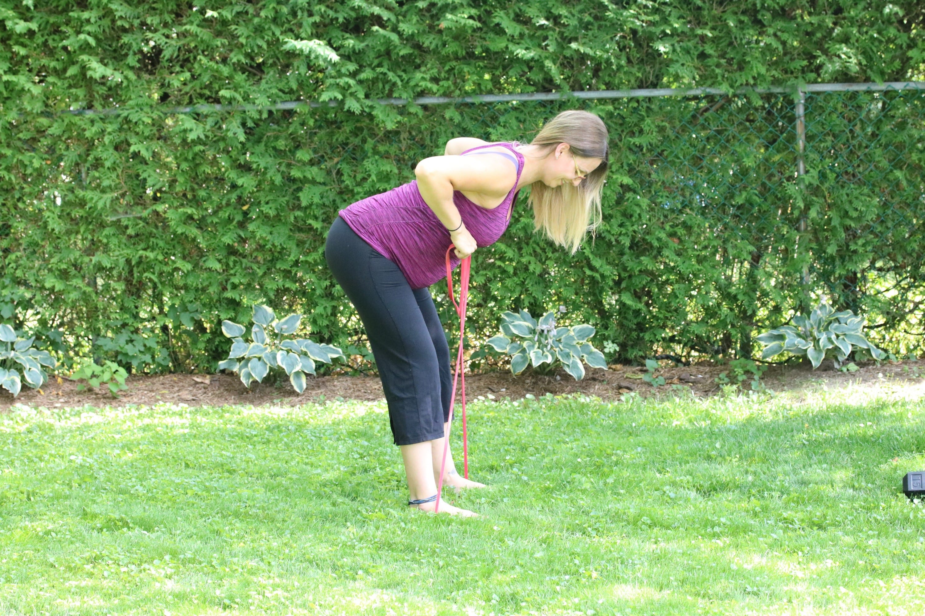 Pregnant lady performing a resistance band exercise outside
