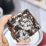 Featured image with text: no-bake peppermint patty bar being held in between two fingers close up
