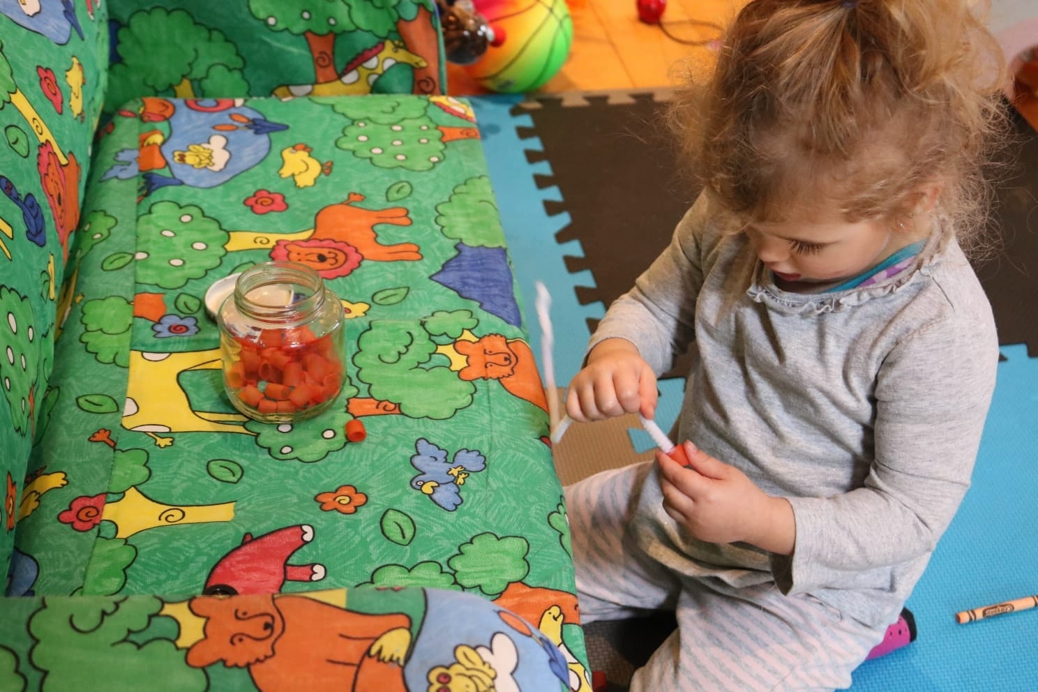 Toddler in grey shirt and pants threading colored noodles onto a pipe cleaner