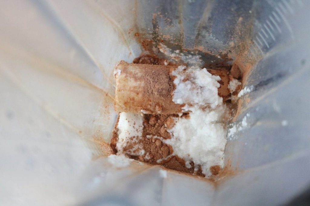 Frozen banana, ice and coconut milk in a blender