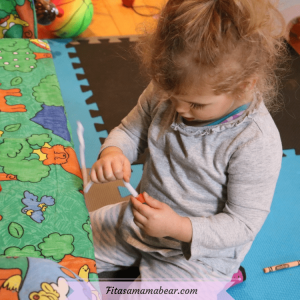 Featured image with text: toddler in a grey shirt threading noodles onto a pipe cleaner