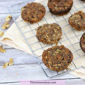 Gluten-free zucchini muffins on a cooling rack over a peach linen with walnuts around it