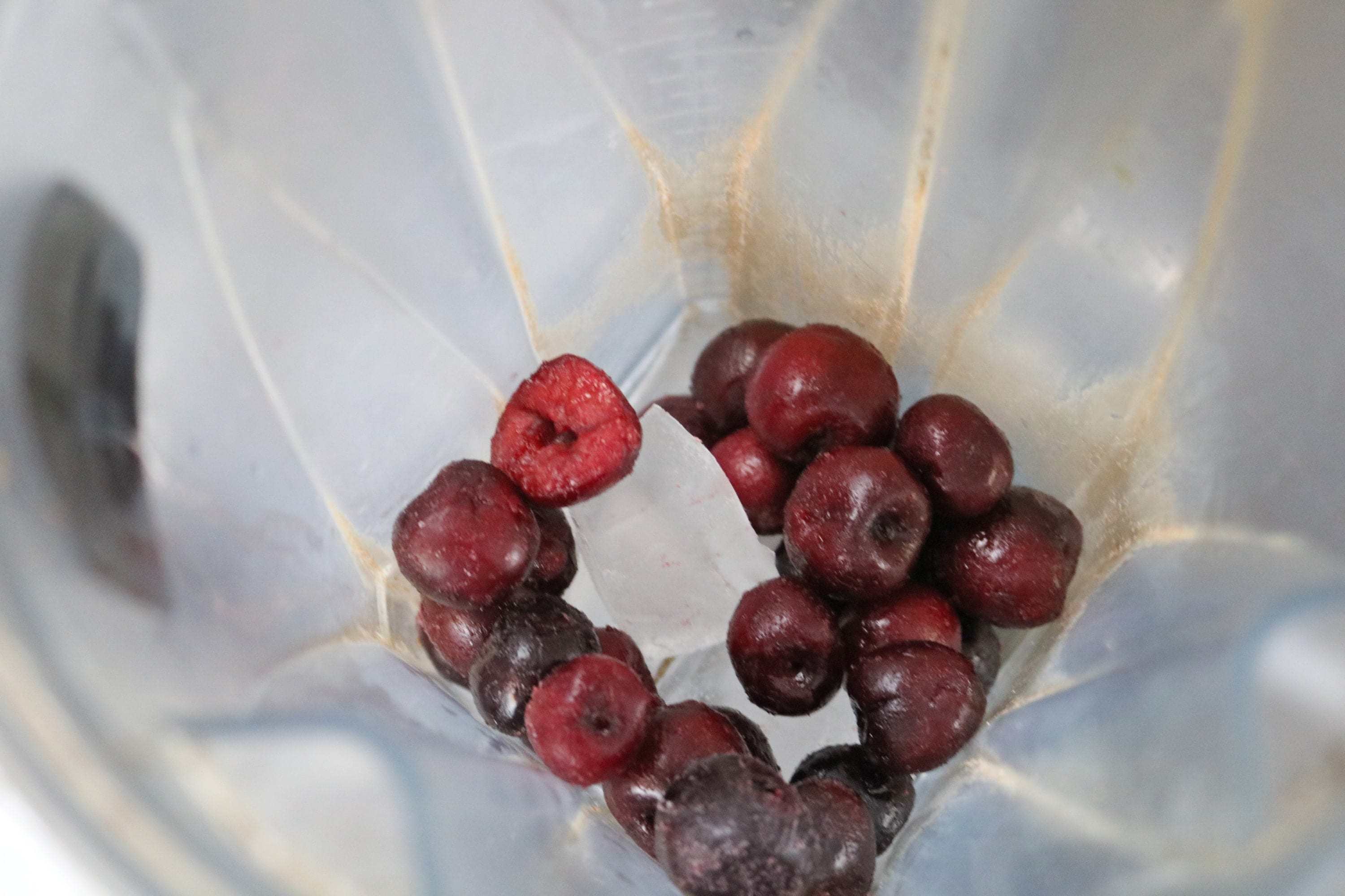 Frozen cherries in a blender with ice cubes