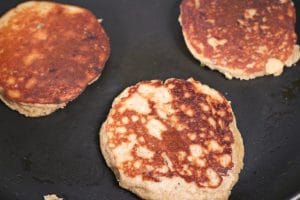 Three banana pancakes cooking in a frying pan after having been just flipped