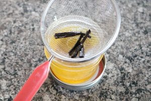 small glass jar with homemade lotion and a small mesh sieve on top straining vanilla bean