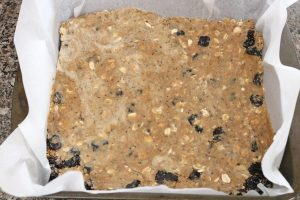 In process image for gluten free homemade protein bars, pressing bars into pan