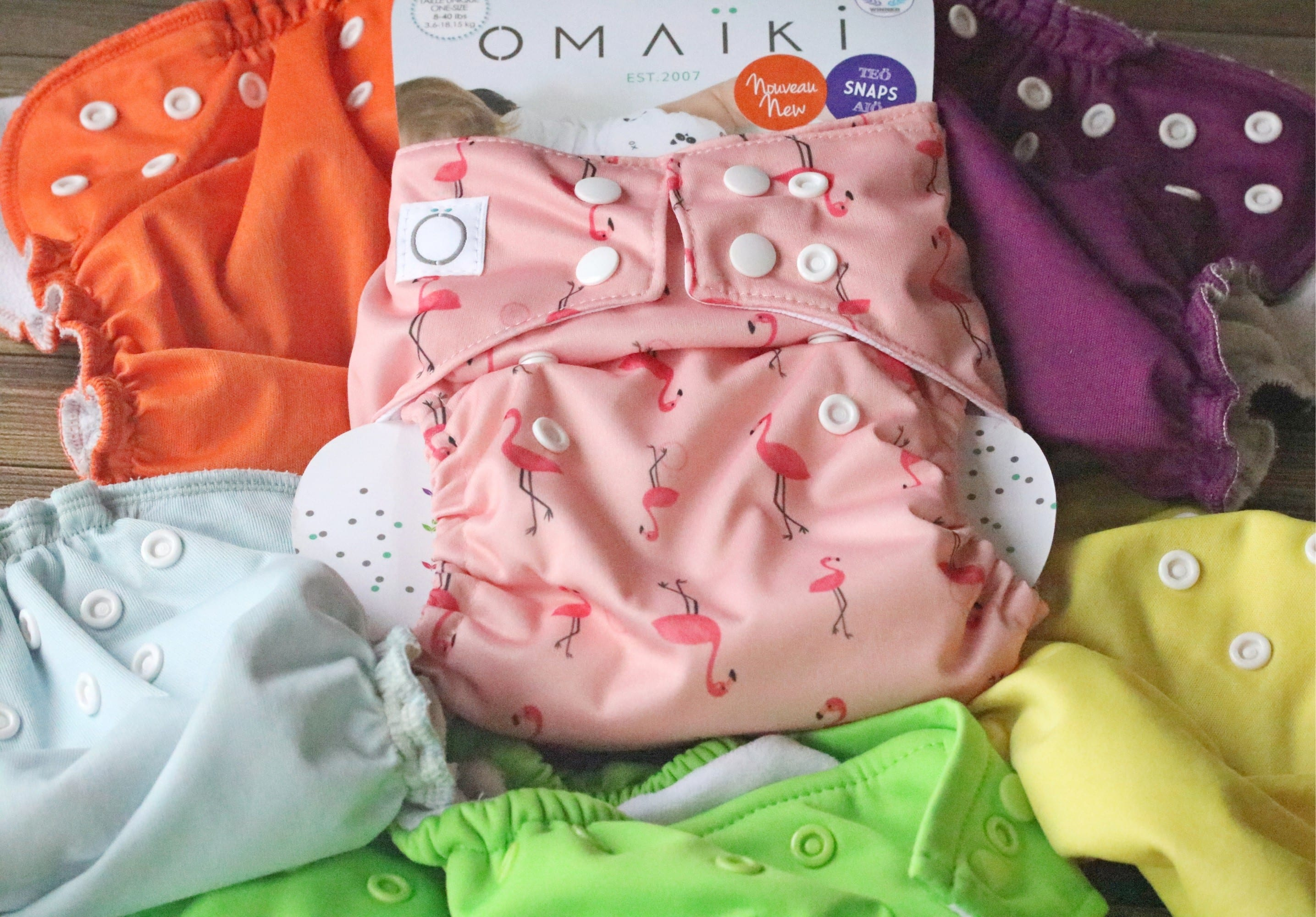 Multiple diapers covers in different colors piled on top of one another