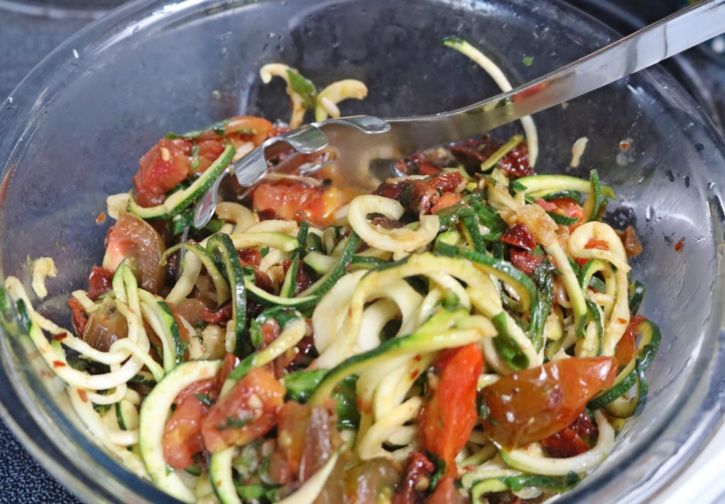 In process image for zucchini noodles pasta: pasta in a pot on the stove being stirred