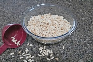In process image for rice krispie squares, bowl of rice puffs spilled over with a red measuring cup