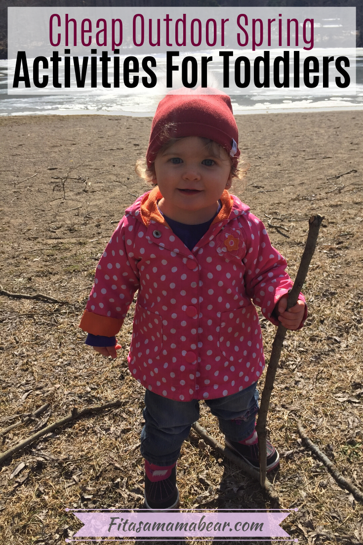 Facebook image with text: toddler in a pink jacket and red hat outside on a hike with a stick as a spring activity