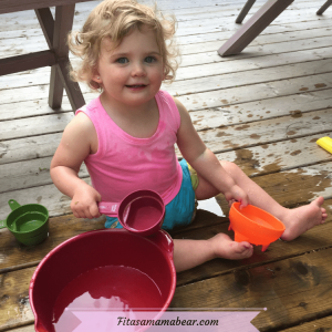 Featured image with text: toddler in pink shirt and blue shorts playing with a bucket of water outside