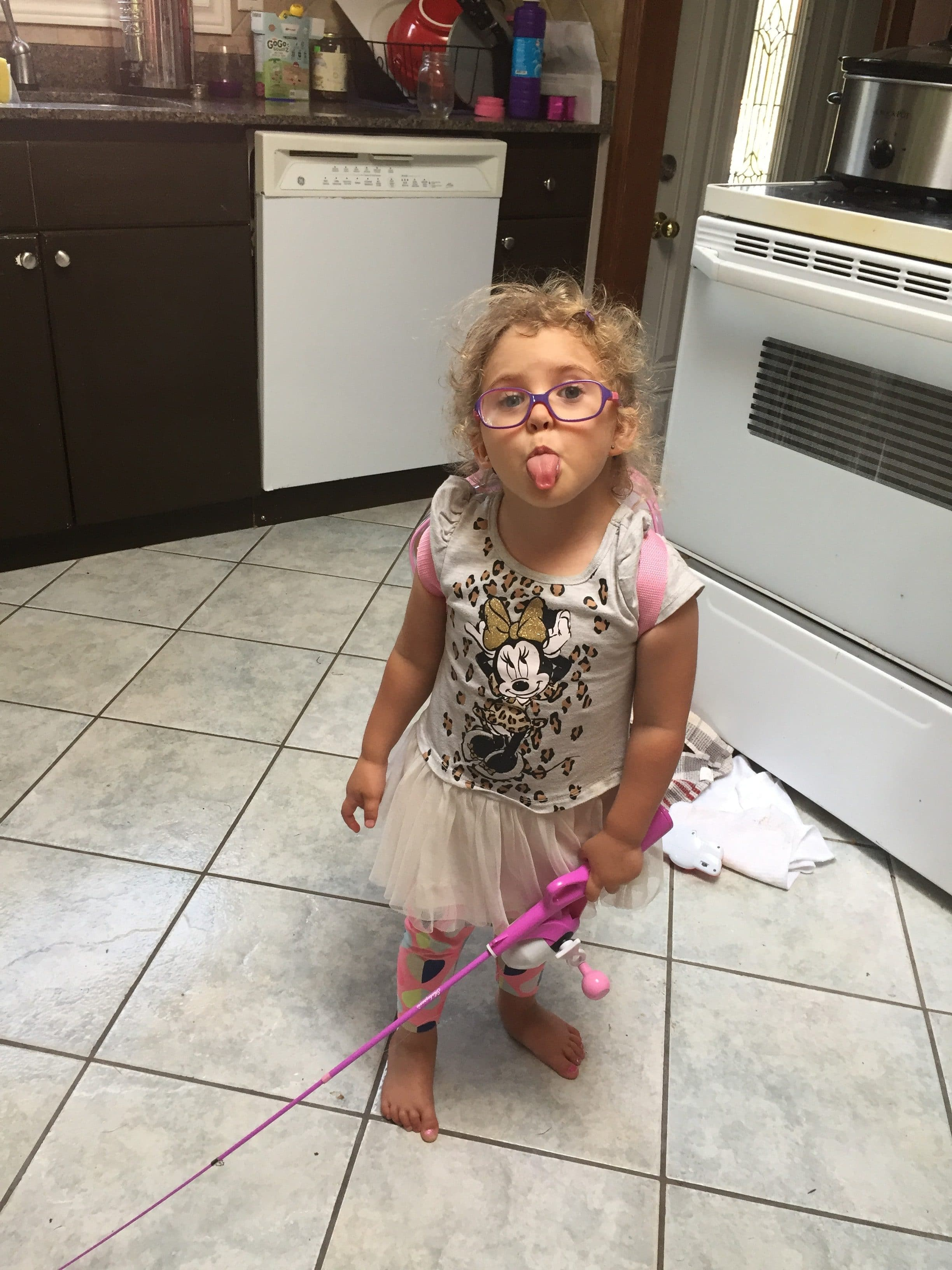 Rainy day activities- a toddler in a white Mickey dress with a fishing pole