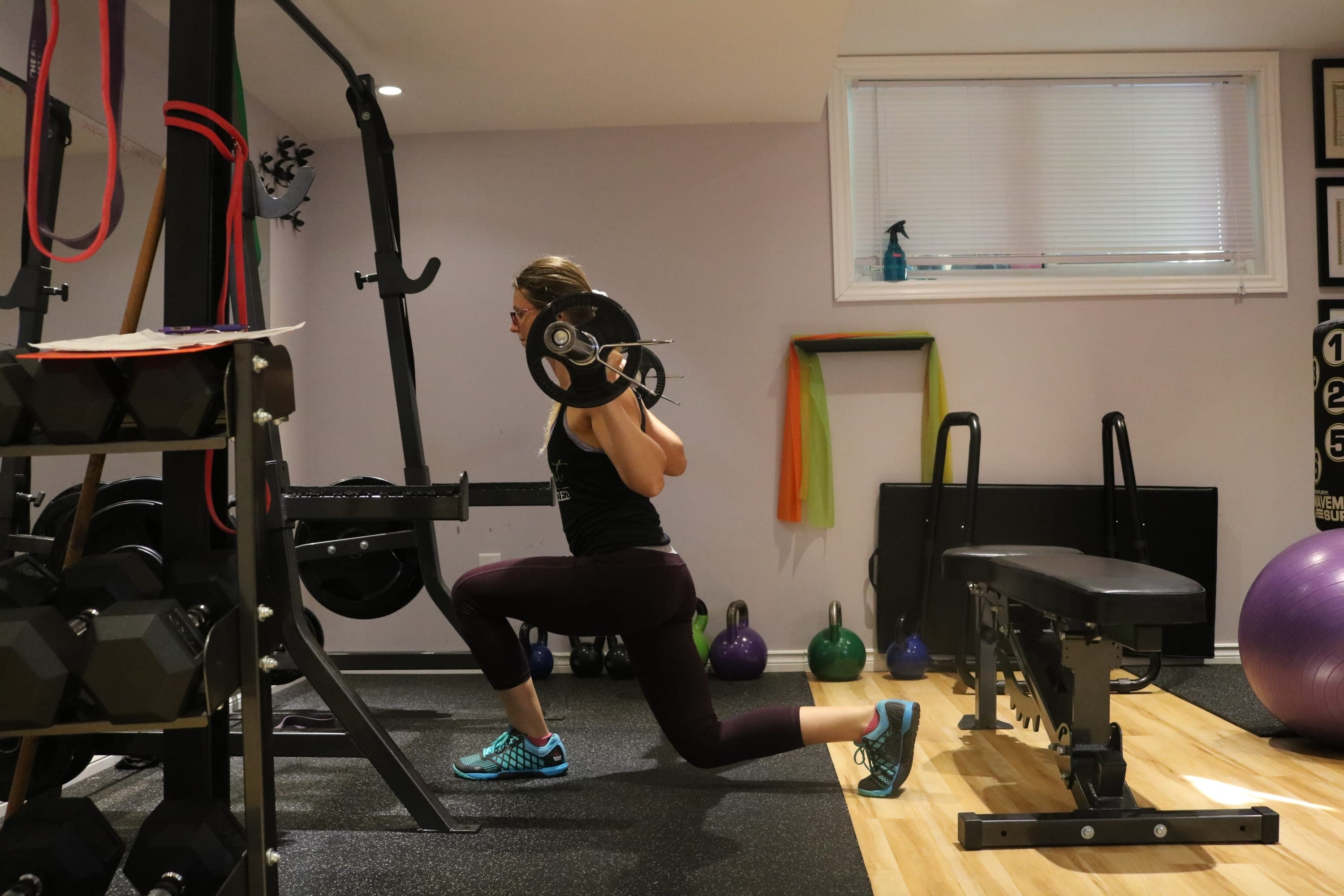 Woman in dark clothes in the gym performing a lunge variation with a barbell
