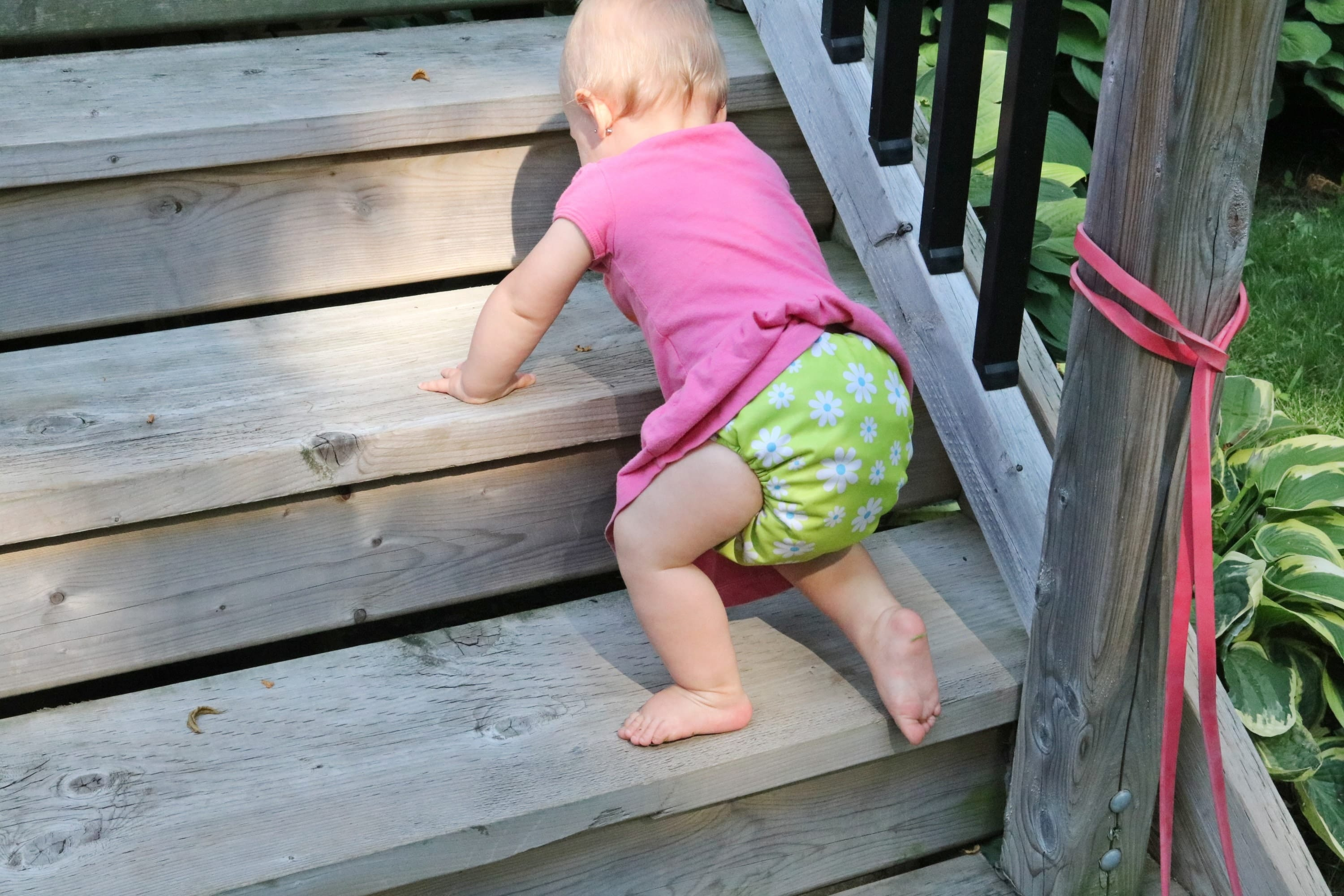 Baby in a pink shirt and green cloth diaper crawling up wooden stairs outside