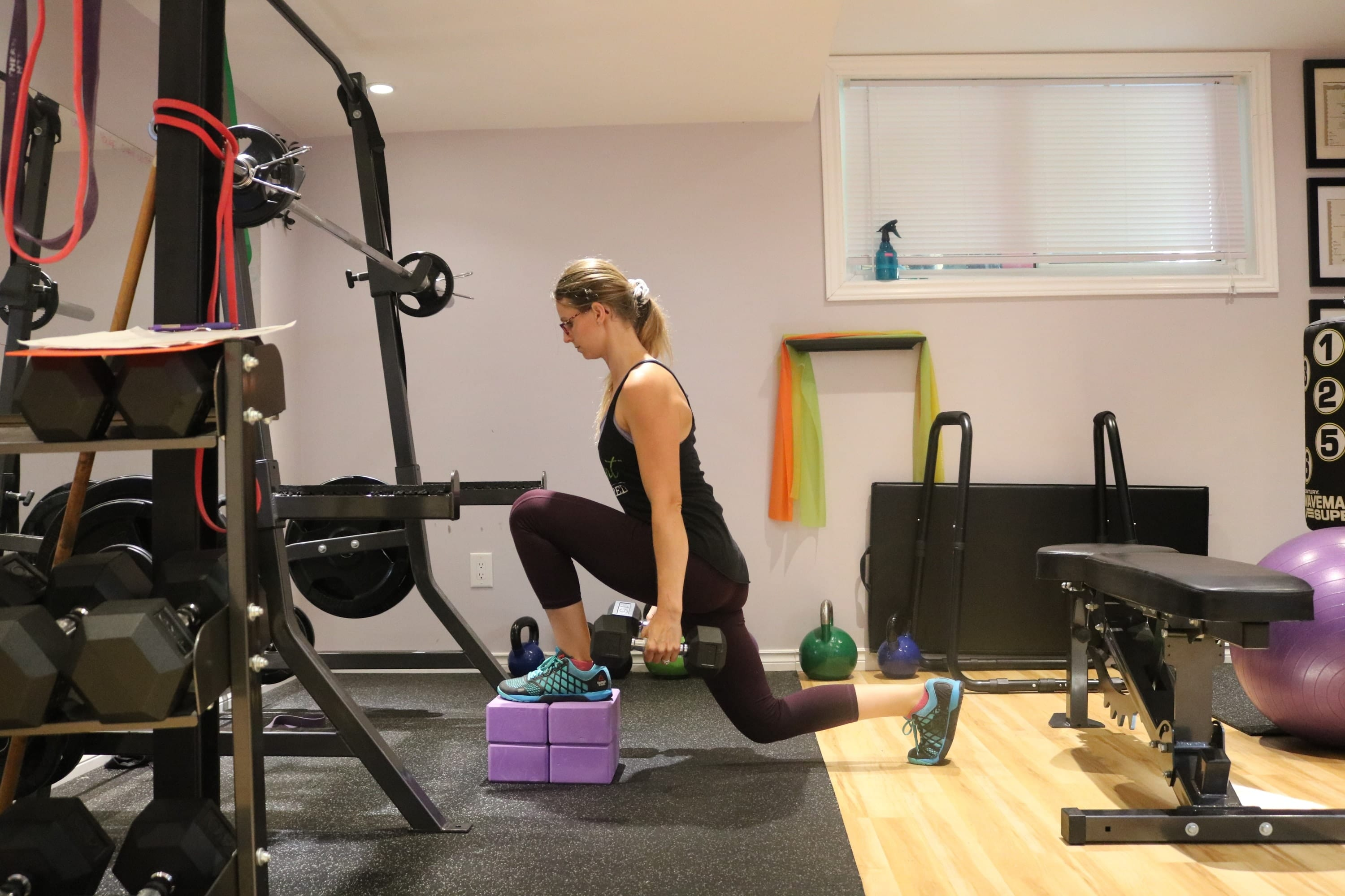 Woman in dark clothes in the gym performing a deficit lunge with dummbells