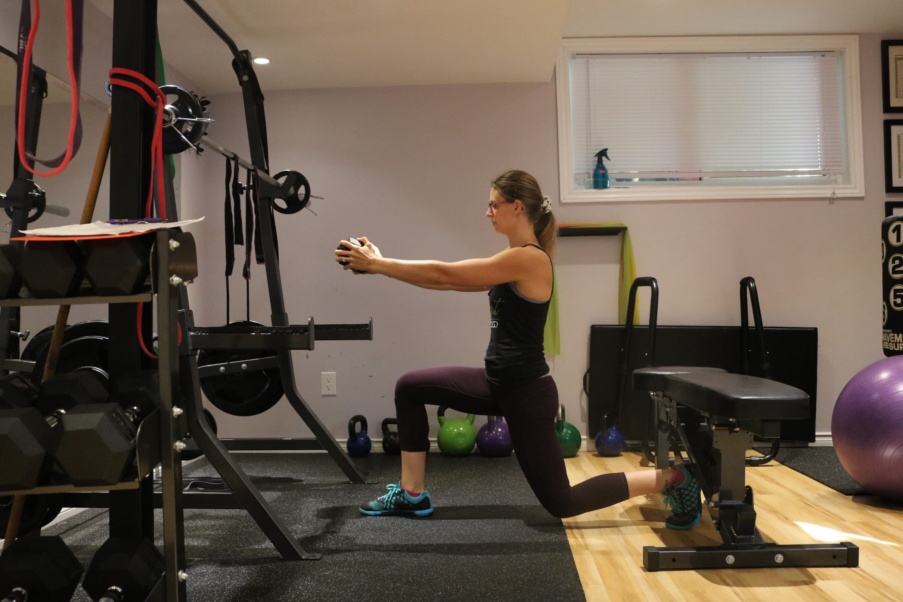 Woman in dark clothes in the gym performing a lunge with a dumbbell