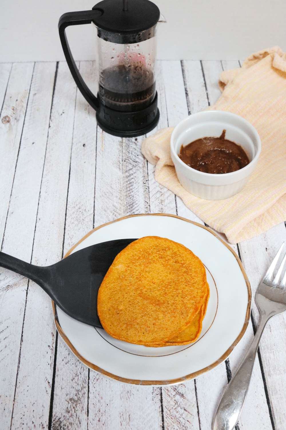 One pumpkin pancake being placed on a white plate by a black spatula