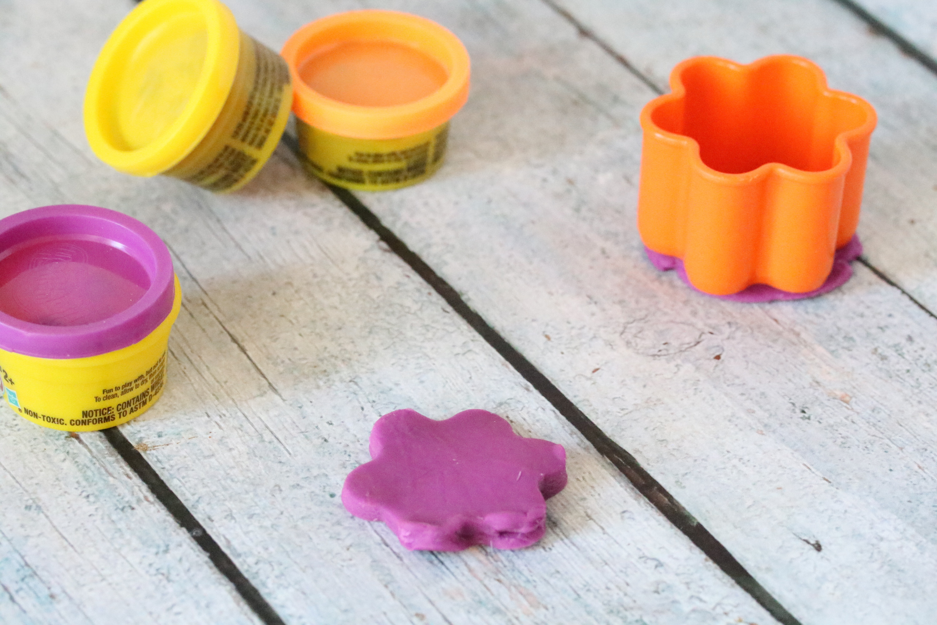 Three playdough containers wtith a purple playdough flower and flower mold.