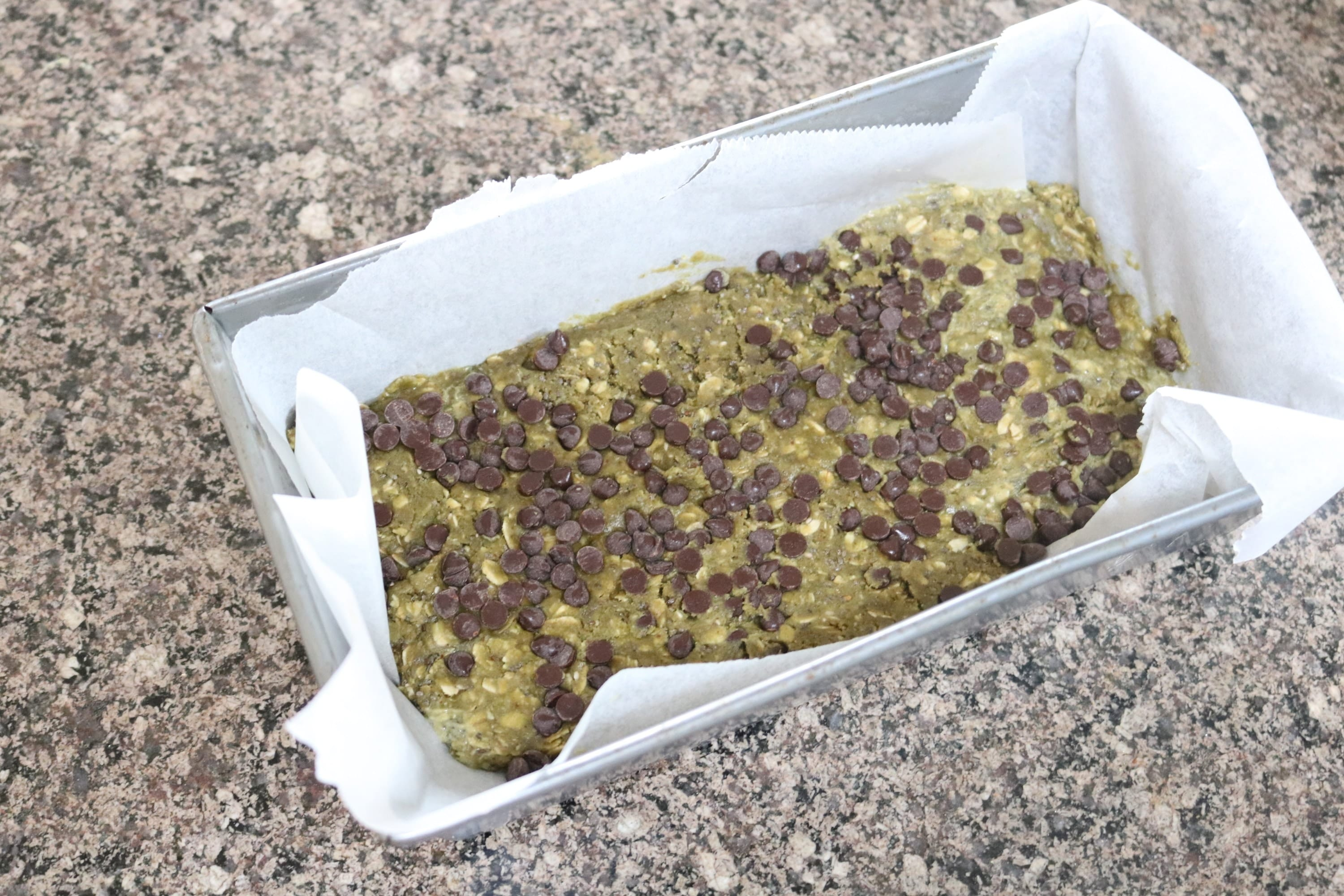 No-bake energy bars in a pan lined with parchment paper and topped with chocolate chips