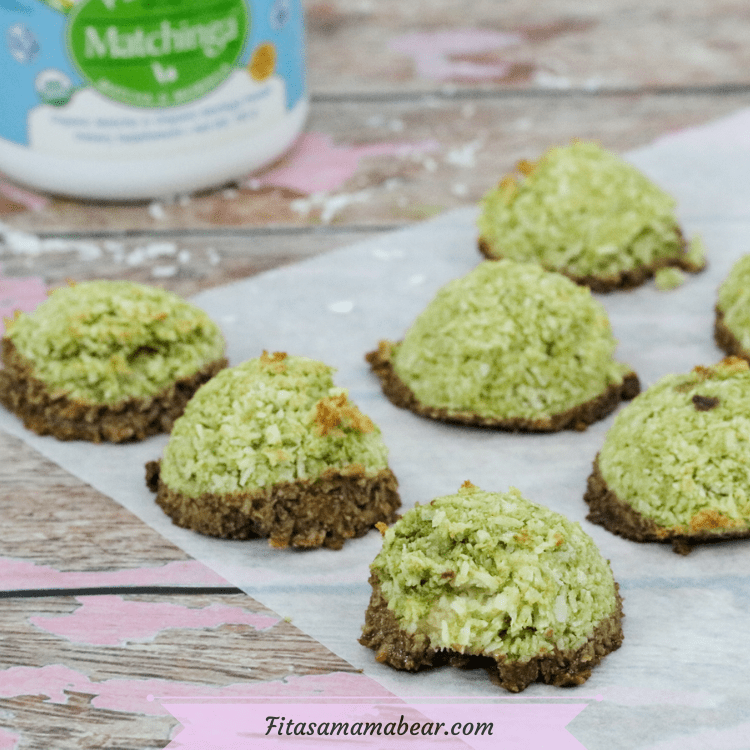 Featured image with text: green coconut macaroons dipped in chocolate on parchment paper with a container of energy-boosting matchinga behind them