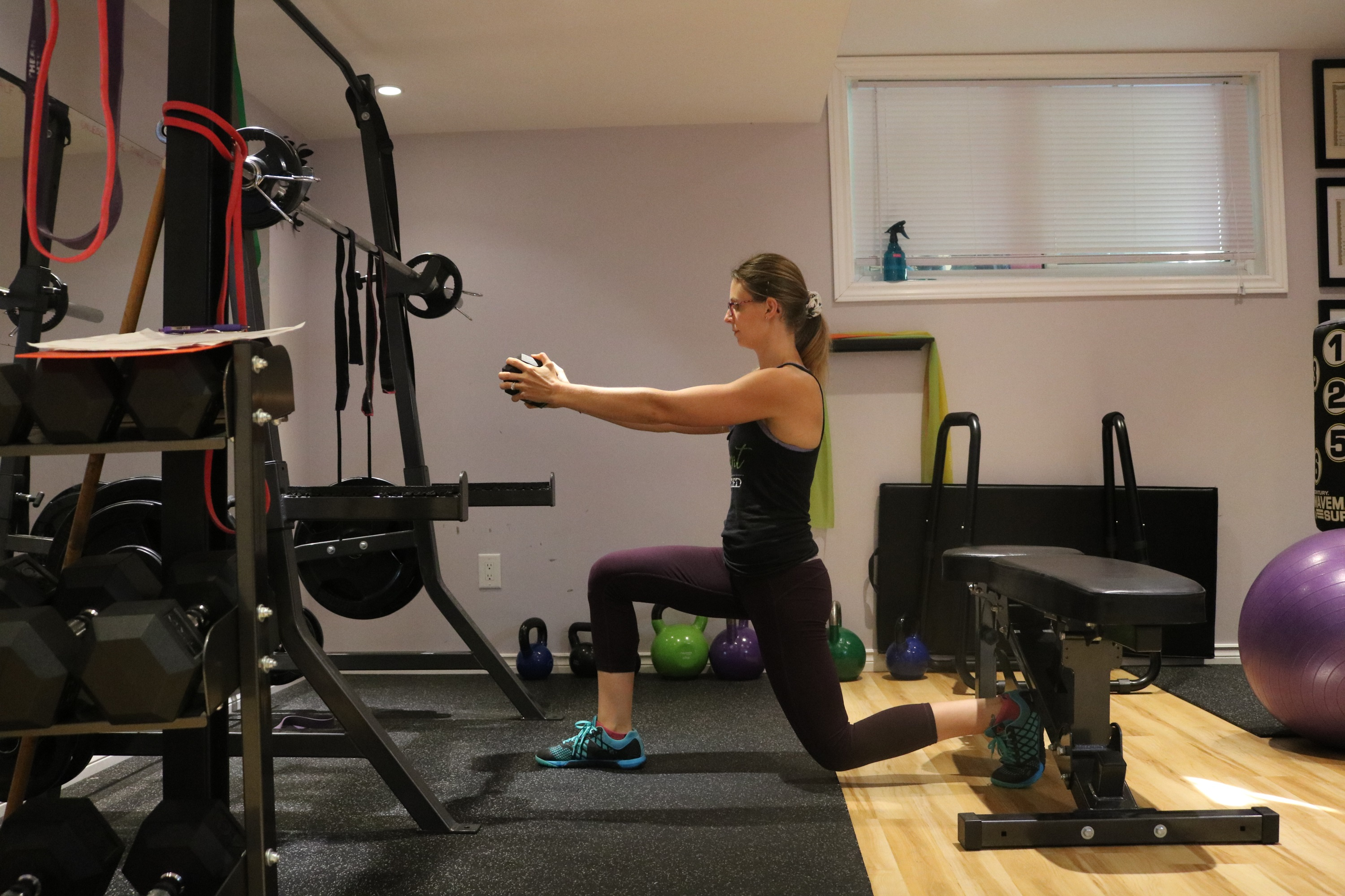 Woman in a home gym performing a lunge with a dumbbell pressed out in front of her